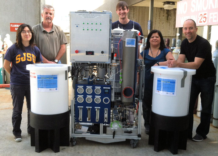Flynn (second from left) and other researchers stand next to a forward osmosis water recycling system, a membrane-based passive wastewater treatment system. Photo courtesy of Flynn, NASA.