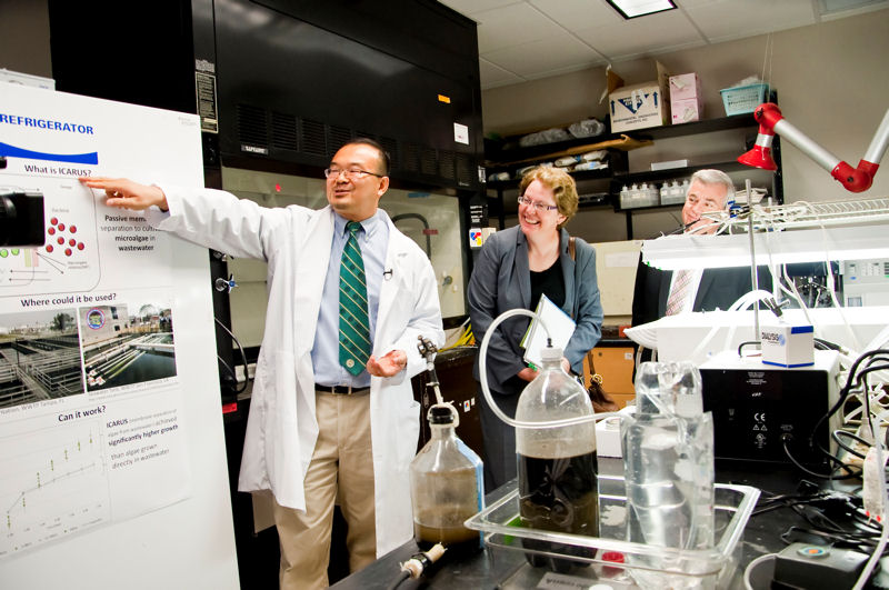 From left, Daniel Yeh, USF associate professor of civil and environmental engineering presents information about his team's NEWgeneratorTM, which converts wastewater into nutrients, clean water, and energy; and work to integrate wastewater treatment and algae biofuel production through the Isolated Cultivation of Algal Resources Utilizing Sewage process, to Stoner and Eger. Photo courtesy of Blodgett.