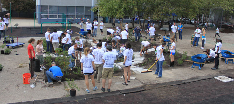 Approximately 110 volunteers helped remove a concrete layer subsurface; lay topsoil; place 13 different types of plants; lay stone pavers; pick up neighborhood trash; and add fencing for the project. Photo courtesy of Falconer.