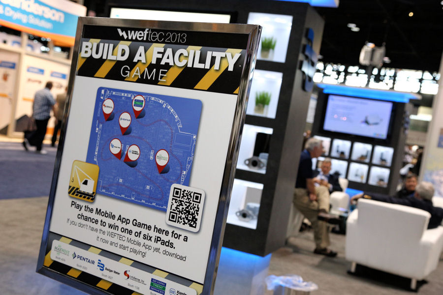 "Signs advertising the ""Build a Facility"" game were placed throughout the WEFTEC 2013 exhibtion floor. Photo courtesy of Oscar Einzig photography."