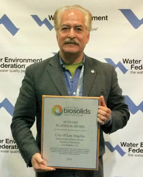 Omar Moghaddam, from the City of Los Angeles, holds the 10 Years Platinum Award presented to the city at WEFTEC 2014. WEF photo/Lisa McFadden.