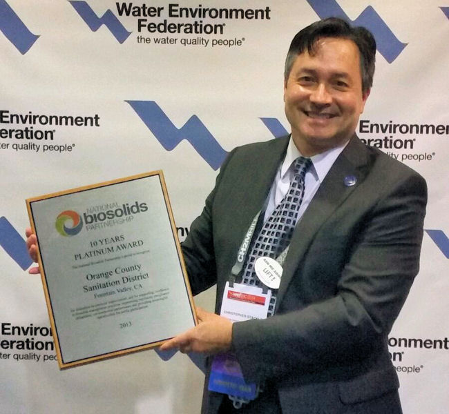 Christopher Stacklin from the Orange County Sanitation District (Calif.) holds the 10 Years Platinum Award presented to the district at WEFTEC<sup>®</sup> 2014. WEF photo/Lisa McFadden.