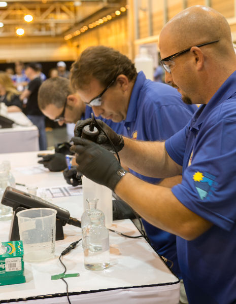 From the left, Jason Scoble, Brian Carlson, and DJ McBride members of the Nevada Water Environment Association Dumplings team compete during the Operations Challenge 2014 Laboratory Event. Photo courtesy of Kieffer Photography.