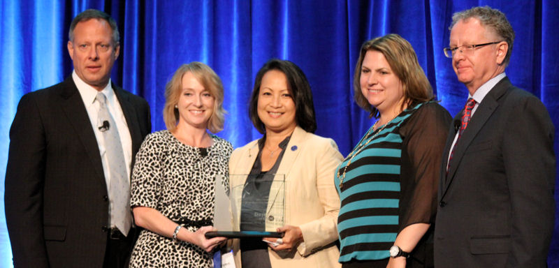 Tran, center, receives the Living Water Award during a NAWC ceremony. Photo courtesy of Tran.