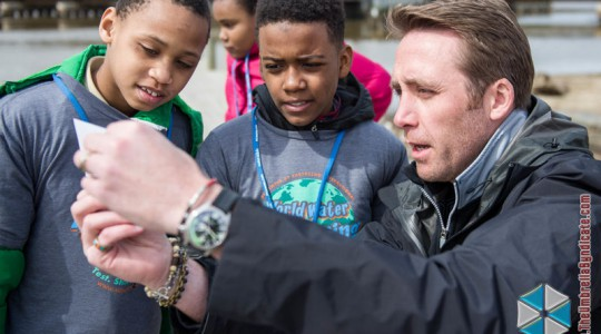 From right, Philippe Cousteau Jr. and students from the Anne Beers Elementary School in Washington, D.C., test water quality along the Anacostia River during an EarthEcho International (Washington, D.C.) 2015 World Water Monitoring Challenge event. Photo courtesy of EarthEcho International.