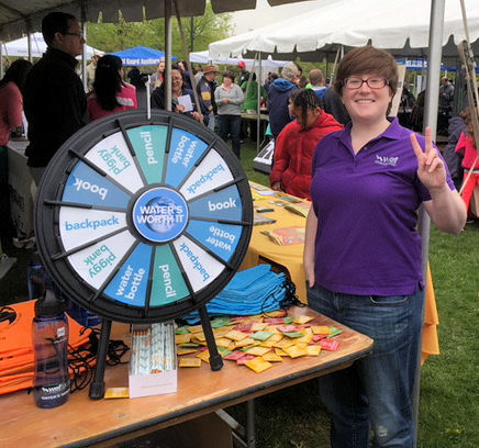 WEF staff member Nicole Jackson stands beside a WATER'S WORTH IT prize wheel. WEF photo/Hurst.