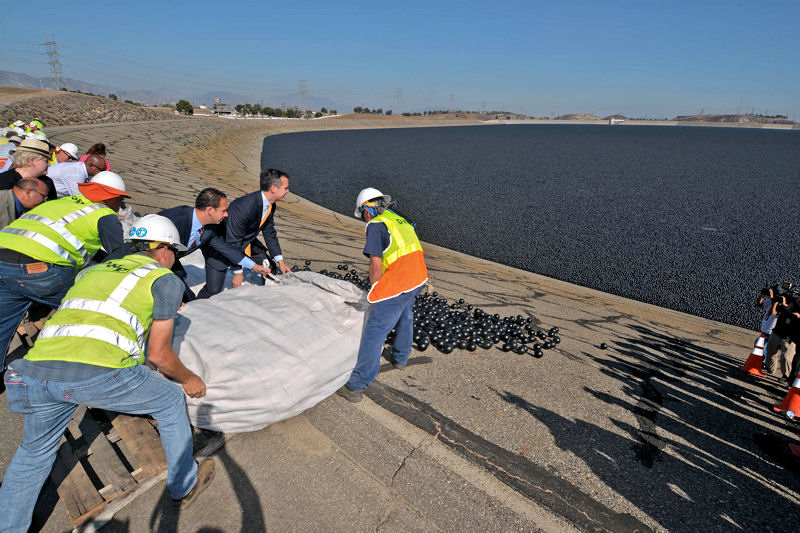 Los Angeles Mayor Eric Garcetti (second from right) helps release black plastic balls — nicknamed shade balls — into the Los Angeles Reservoir. Photo courtesy of the Los Angeles Department of Water and Power.