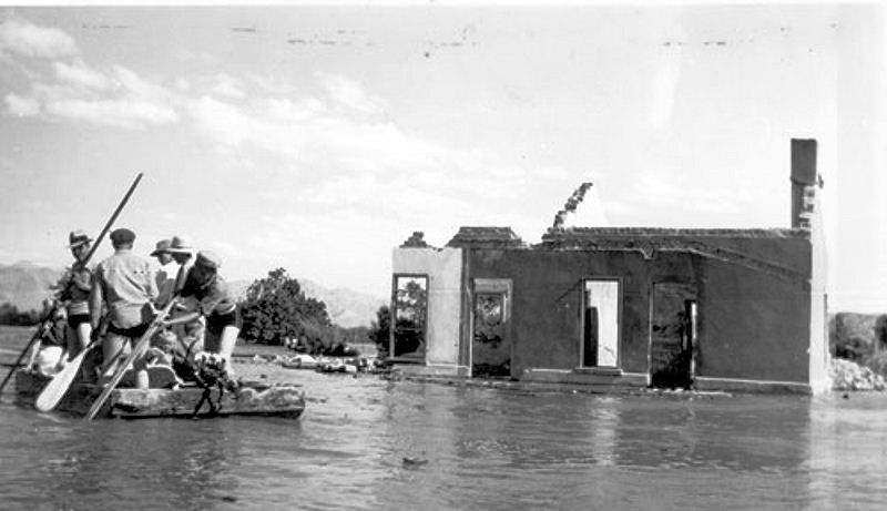 A salvage crew rafts through St. Thomas near the ruins of a building as Lake Mead begins to submerge the town in June 1938. Photo courtesy of the Lake Mead National Recreation Area.