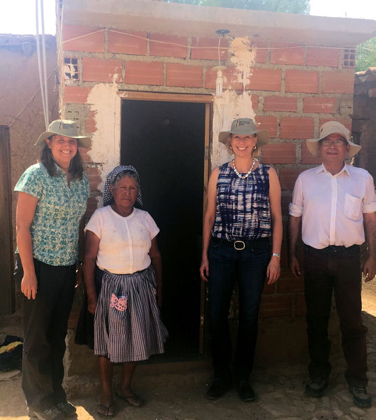 Allen (third from left) and two colleagues stand in front of Doña Carmen's new toilet in Bolivia. Photo courtesy of Allen.