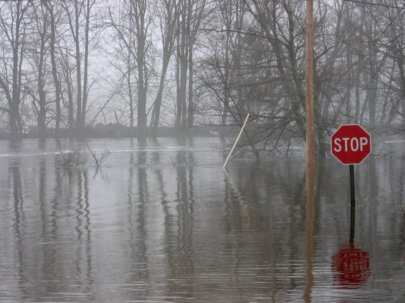 A stop sign at the end of School House Hill Rd in Turner, Maine shows a flooded road near a U.S. Geological Survey (USGS) gaging station on the Nezinscot River. Photo courtesy of Nick Stasulis, USGS.