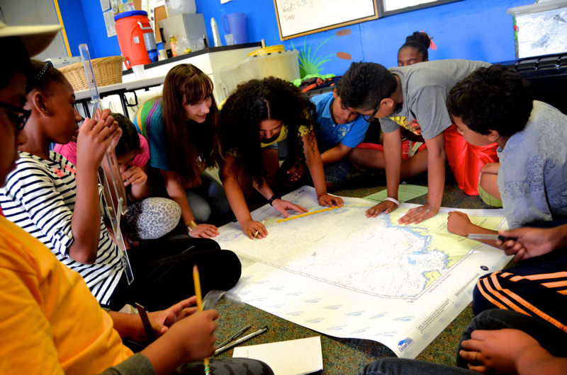 The On-Water Classroom creates unique and hands-on learning experiences for students such as using maps to examine the Bronx River. Photo courtesy of Rocking the Boat.