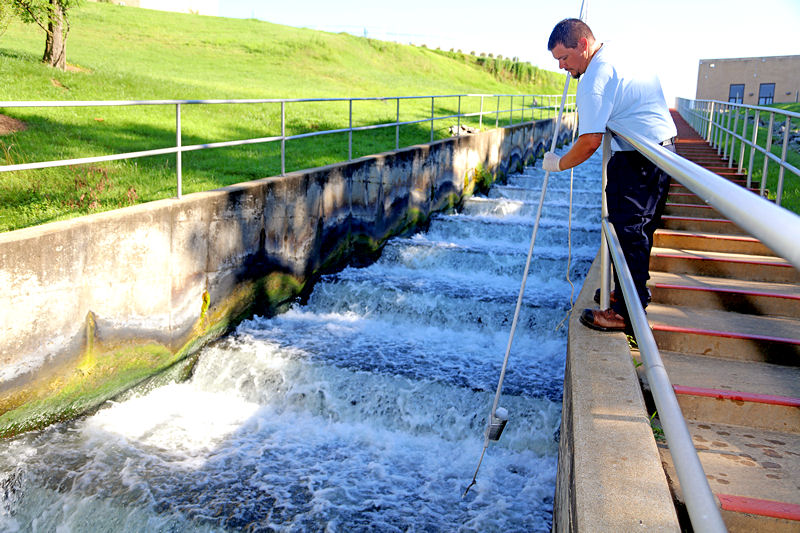 Jacob Oney, wastewater operator trainee, samples the outfall at the H.L. Mooney Advanced Water Reclamation Facility in Woodbridge, Va. Photo courtesy of Kipp Hanley, Prince William County Service Authority.