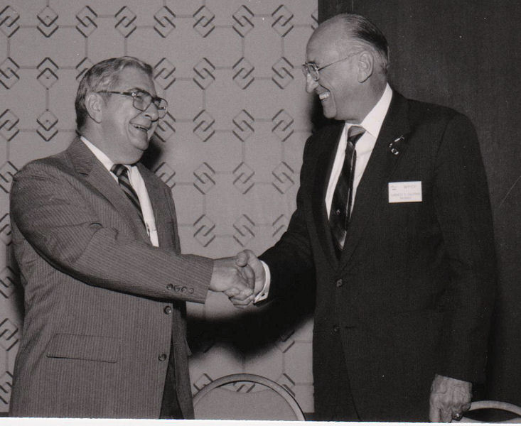 Robert, WEF executive director, shakes the hand of Ernie Gloyna, WEF president from 1983 to 1984 during a WEF event in New Orleans during 1984. WEF Archives photo.