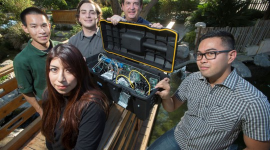 Cal Poly Pomona Professor Dan Manson (third from left) stands with students, from left, Jose Ybanez, Raissa Englehard, Nate Hom, and Joe Needleman. The students built a device that replicated the functions of a water-treatment plant for the Passcode Cup cybersecurity competition. Photo courtesy of Tom Zasadzinski.
