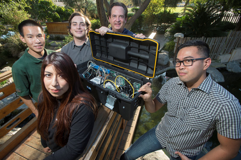 California State Polytechnic University, Pomona professor Dan Manson (back) stands with students, from left, Nate Hom, Raissa Englehard, Joe Needleman, and Jose Ybanez. The students built a device that replicated the functions of a water treatment facility for the Passcode Cup cybersecurity competition. Photo courtesy of Tom Zasadzinski.