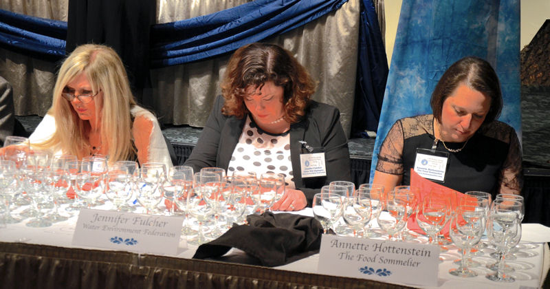<i>WEF Highlights</i> Editor Jennifer Fulcher (center) joins other judges to taste tap, bottled, and sparkling water at the Berkeley Springs (W.Va.) International Water Tasting competition. Photo courtesy of Travel Berkeley Springs.