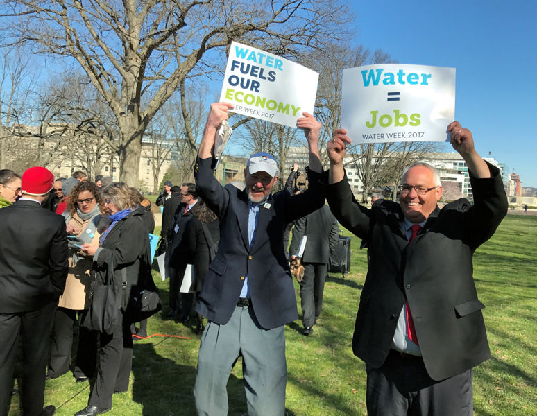 From left, Maine Water Environment Association members Mac Richardson and Chris Littlefield carry signs showing the economic benefits of water during the Water Week 2017 Rally for Water. Photo courtesy of Matt Timberlake, president of Ted Berry Company Inc. (Livermore, Maine).