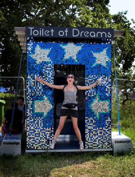 A festival-goer poses in front of WaterAid's 'Toilet of Dreams' at the 2017 Glastonbury festival. Photo courtesy of WaterAid, Emily Graham.