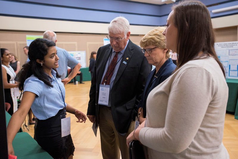 Condon (third from right) listens to a student contestant describe her water research as a judge at the 2017 U.S. Stockholm Junior Water Prize competition. Photo courtesy of AOB Photo.