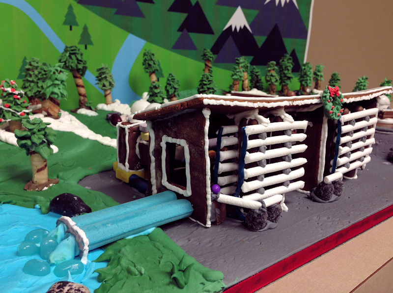 "The reverse osmosis assembly was constructed using candy cigarettes inside a gingerbread shed. Cleaned ""water"" is released by blue candy cigar pipes into a blue icing reservoir. Photo courtesy of Brown and Caldwell."