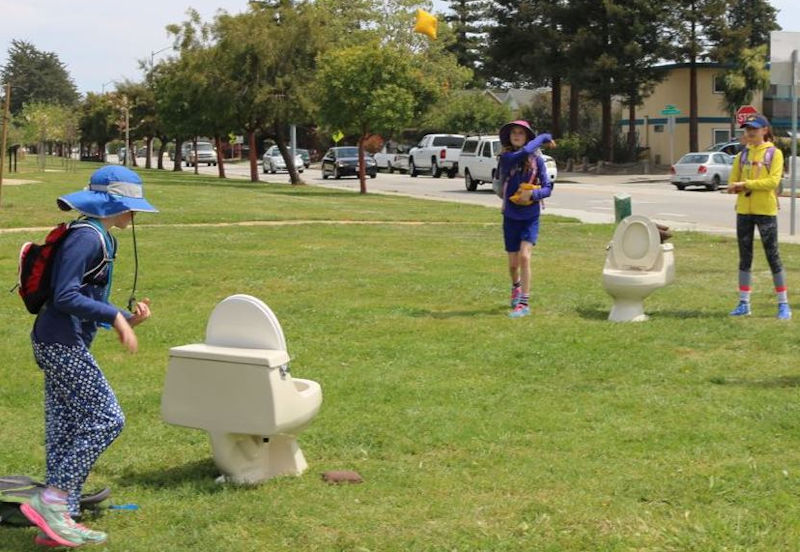 """The Follow the Flush event featured interactive games and activities such as the toilet toss game where players could throw bean-bag """"mud-pies"""" into empty toilet bowls. City of Santa Cruz."""
