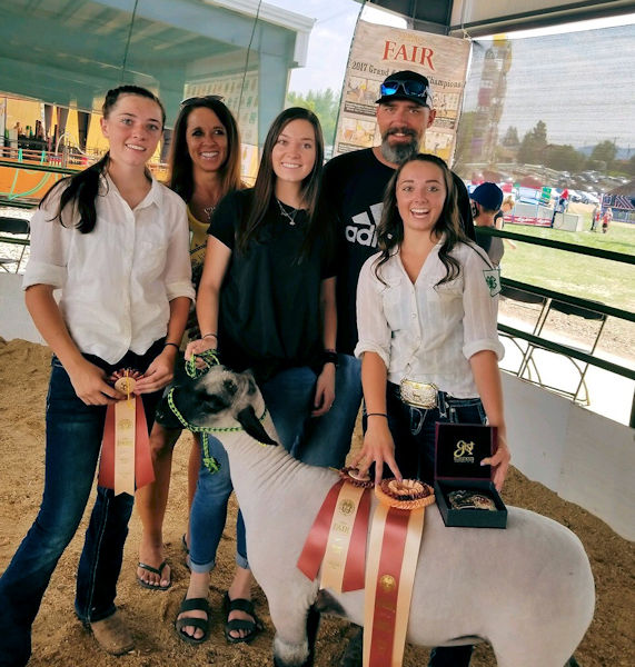 Cody Snyder (back right) and his wife, Jill Snyder (back left), attend a county fair with their three daughters where their sheep are shown. Photo courtesy of the Snyder family.