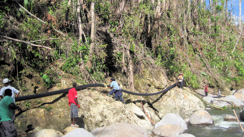 A new distribution pipe is being hung along the river during the first Operators Without Borders trip in December 2017. Photo courtesy of Misuraca.