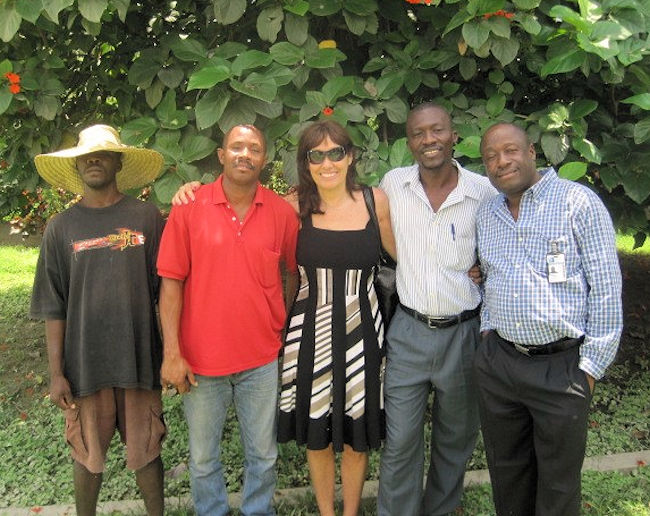"Jenkinson stands with operators at a pumping station in Haiti. Operators Without Borders is an organization of ""operators supporting operators,"" she said. Photo courtesy of Jenkinson."